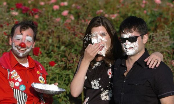 <p>Ms. Drake (center), after receiving a pie in the face from Jusby the Clown (left). At right is Ms. Drake&#8217;s husband, <cite>Core</cite> author Kassten Alonso.</p>